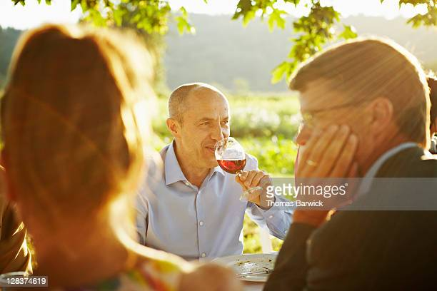 Mature man sitting at outdoor table drinking wine