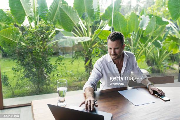 mature man sitting at table in front of lush garden, using laptop - premium access stock pictures, royalty-free photos & images