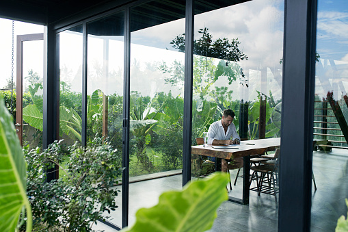 Mature man sitting at table in front of lush garden, writing - gettyimageskorea