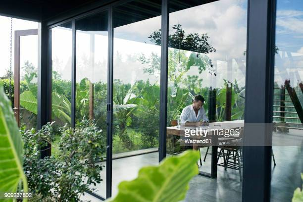 mature man sitting at table in front of lush garden, writing - gedeihend stock-fotos und bilder