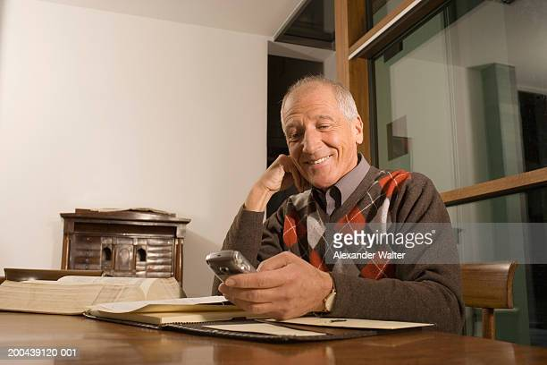 Mature man sitting at table looking at mobile phone, smiling