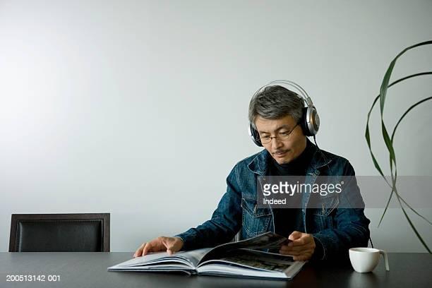 成熟した男性のシッティングエリア、テーブル、読書ば、ヘッドフォン