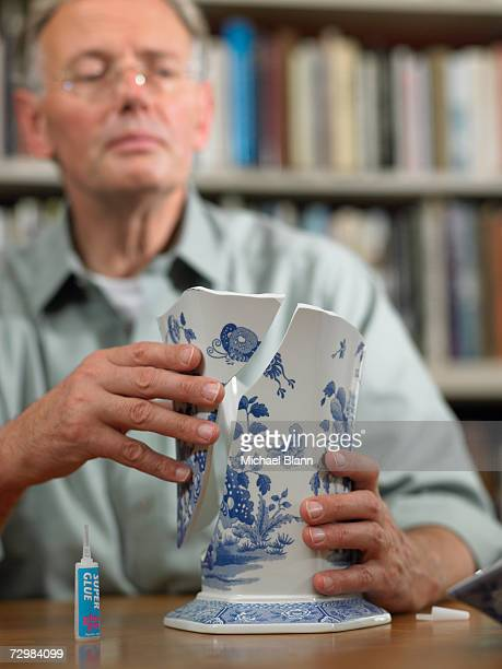 Mature man sitting at table repairing broken china vase