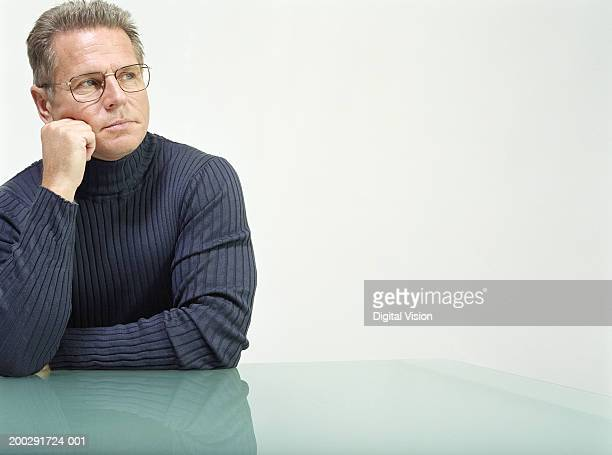 Mature man sitting at table, resting cheek on hand