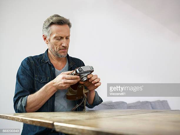 Mature man sitting at table with old camera