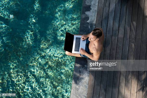 mature man sitting at the poolside, using laptop - premium access stock pictures, royalty-free photos & images