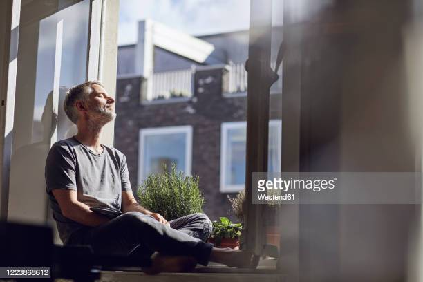 mature man sitting at the window at home with closed eyes - resting stock pictures, royalty-free photos & images
