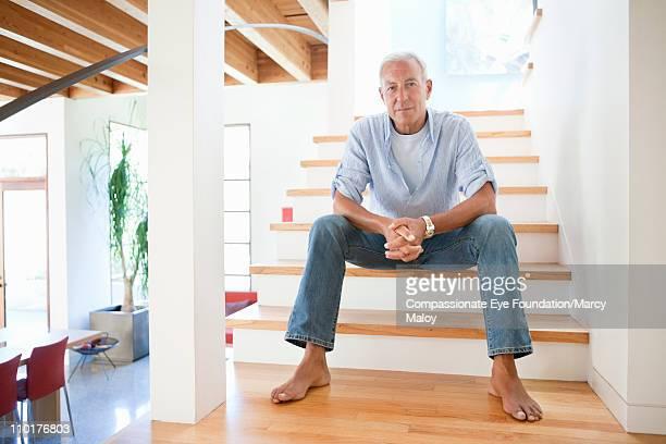 Mature man sitting barefoot on indoor stairway