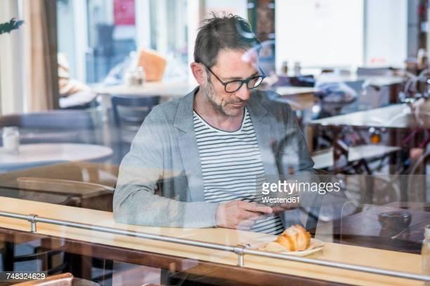 mature man sitting behind window pane of a coffee shop looking at cell phone - barba por fazer imagens e fotografias de stock