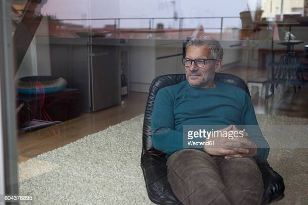 Mature man sitting behind windowpane looking out