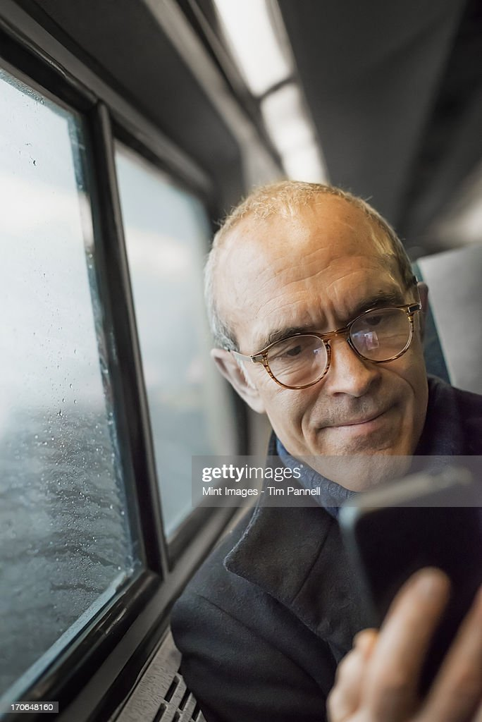 A mature man sitting by a window in a train carriage, using his mobile phone, keeping in touch on the move. : Stock Photo