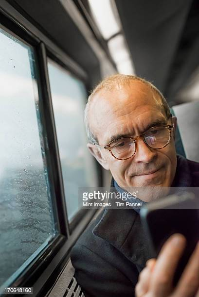 A mature man sitting by a window in a train carriage, using his mobile phone, keeping in touch on the move.