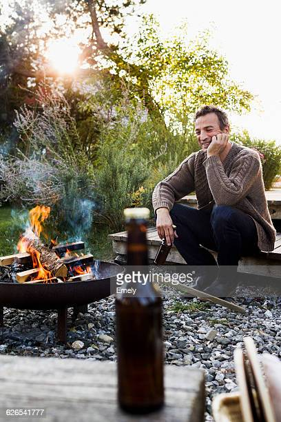 mature man sitting by fire pit with beer, relaxing - fire pit stock pictures, royalty-free photos & images
