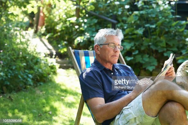 Mature man sitting in a deckchair in his garden