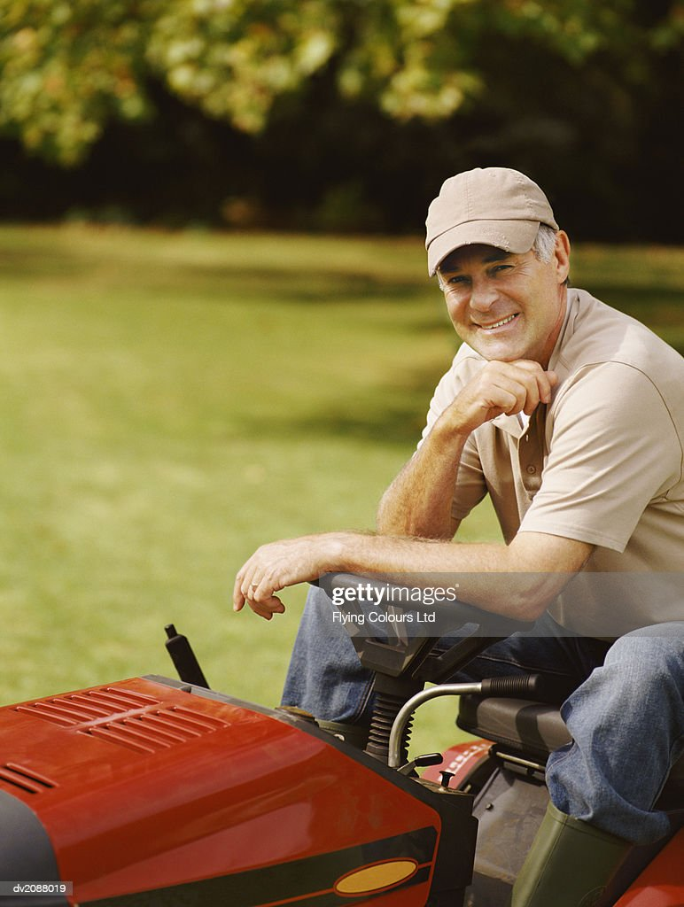 Mature Man Sitting in a Garden on a Lawnmower : Stock Photo