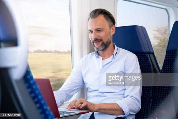 mature man sitting in a train, using laptop - bahnreisender stock-fotos und bilder