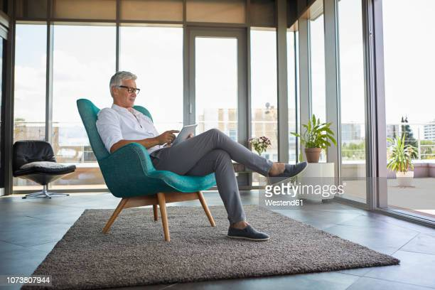 mature man sitting in armchair at home using tablet - only mature men stock pictures, royalty-free photos & images