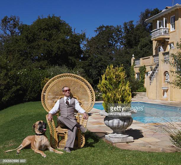 Mature man sitting in armchair with dog at poolside