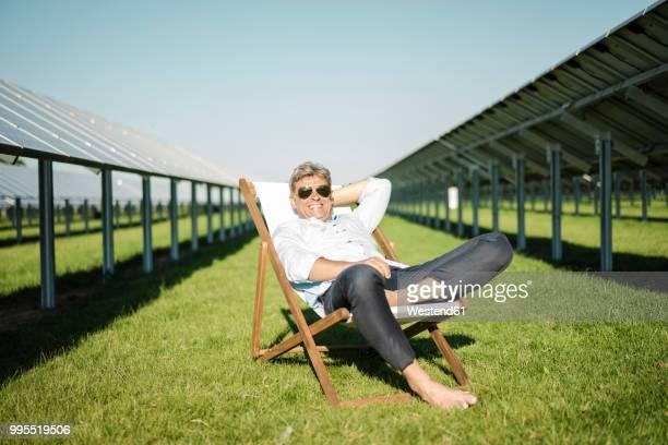 Mature man sitting in beach lounger, solar plant