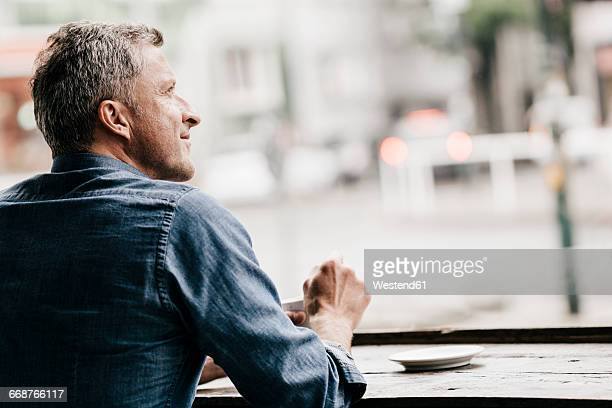 mature man sitting in cafe looking out of window - premier plan net photos et images de collection
