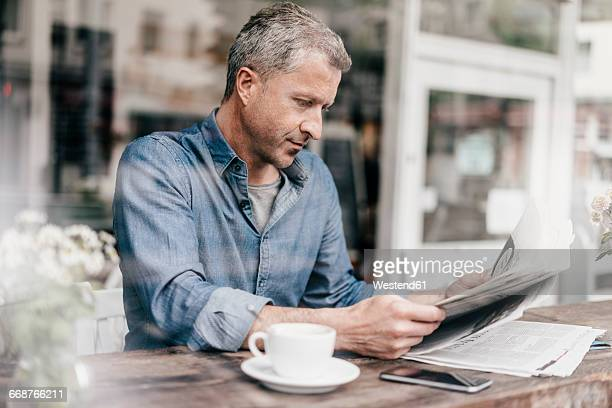 Mature man sitting in cafe reading newspaper