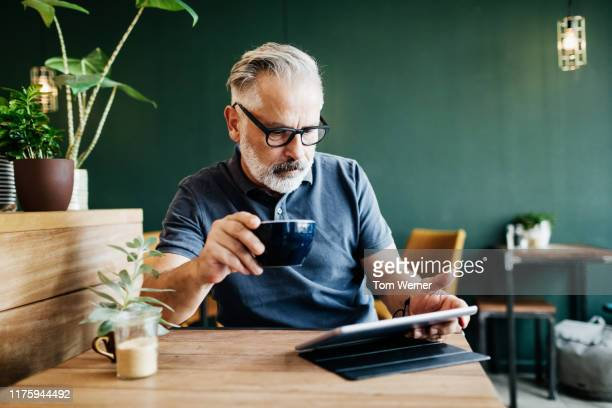 mature man sitting in cafe reading on tablet - using digital tablet stock pictures, royalty-free photos & images