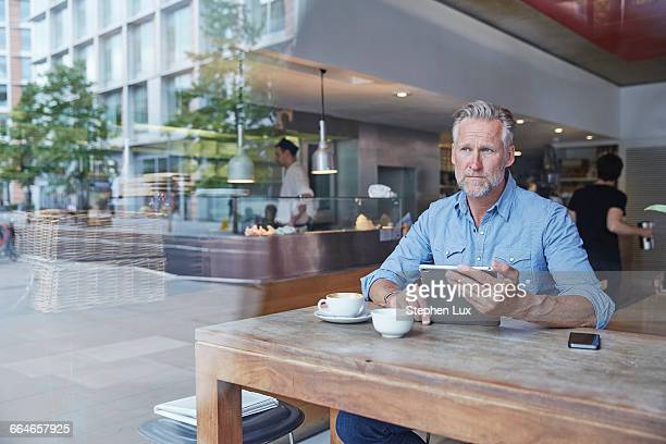 Mature man sitting in cafe, using digital tablet