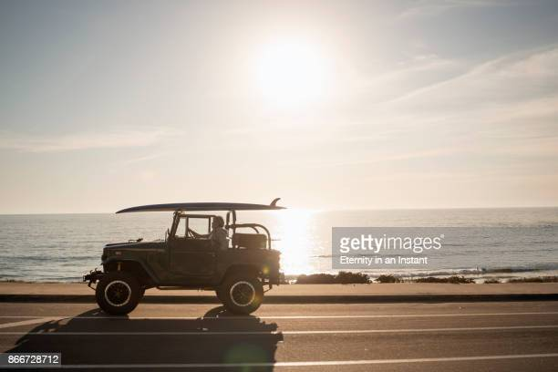 mature man sitting in his land cruiser by the beach - 4x4 stock pictures, royalty-free photos & images