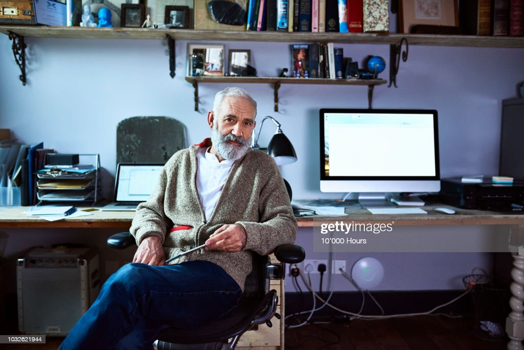 Mature man sitting in home office looking at camera : Stock-Foto