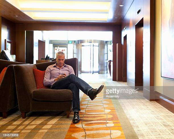 Mature man sitting in hotel lobby, texting.