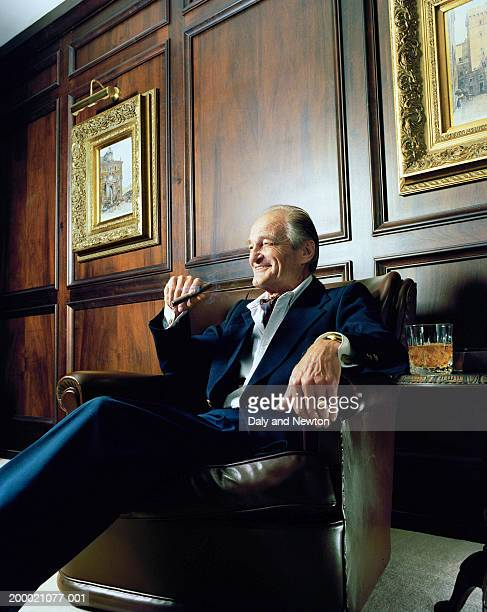 Mature man sitting in leather chair, smoking cigar
