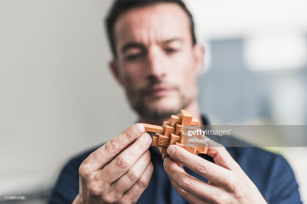 Mature man sitting in office assembling wooden cube puzzle : Foto stock