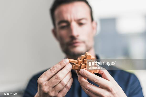 mature man sitting in office assembling wooden cube puzzle - solutions stock pictures, royalty-free photos & images