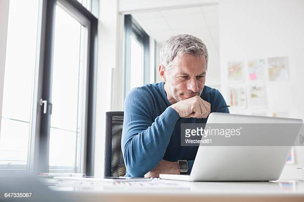 mature man sitting in office using laptop - mature men stock pictures, royalty-free photos & images