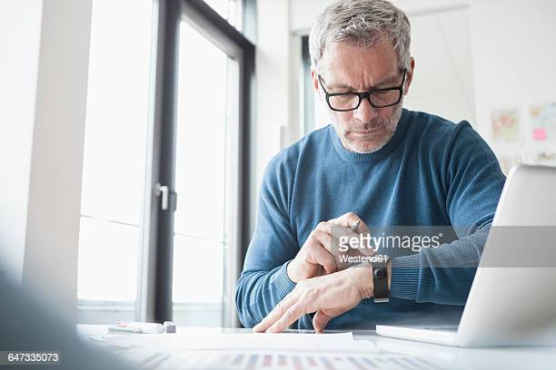 mature man sitting in office working with laptop and smart watch - wearable computer stock pictures, royalty-free photos & images