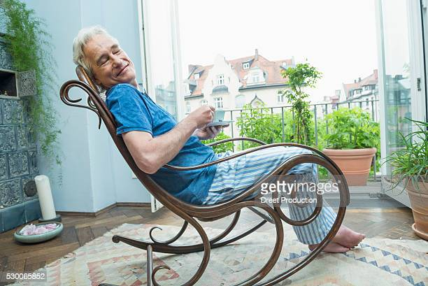 Mature man sitting in rocking chair and holding coffee cup, smiling