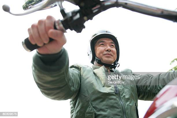 Mature man sitting on a motorcycle, low angle view