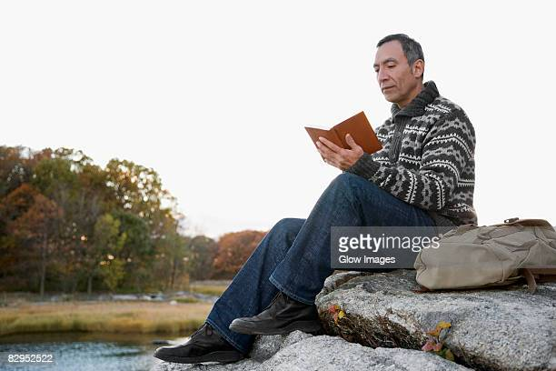 Mature man sitting on a rock and reading a book