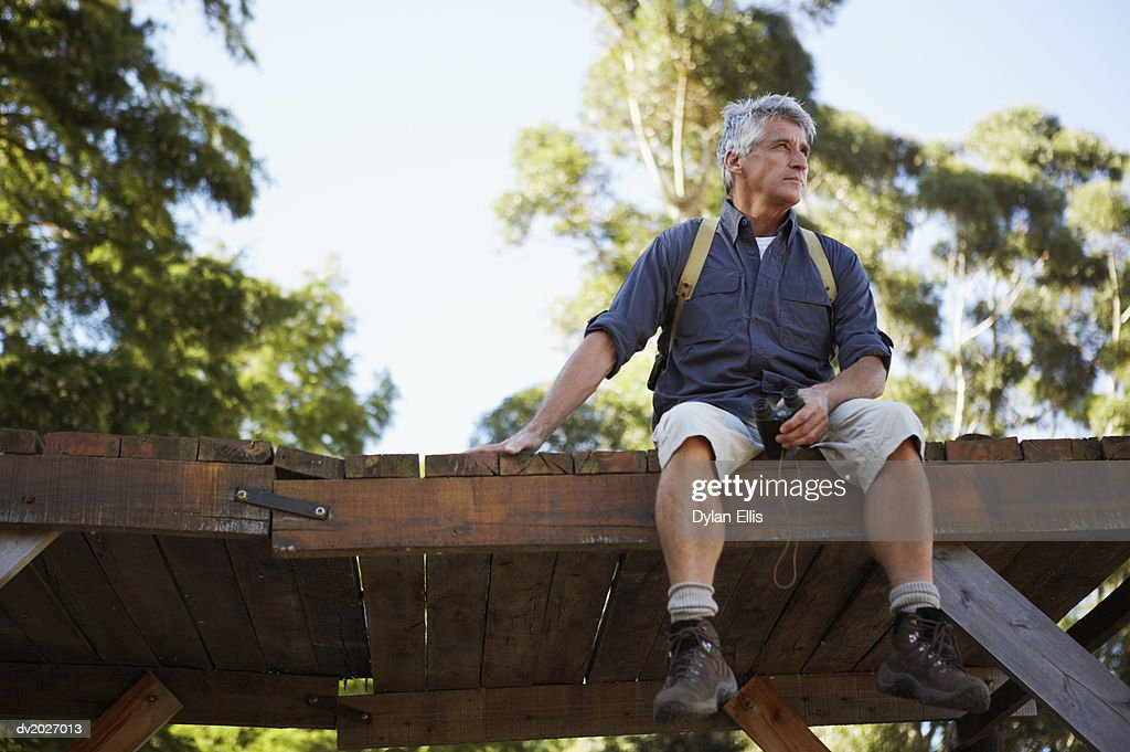 Mature Man Sitting on a Wooden Platform : Stock Photo