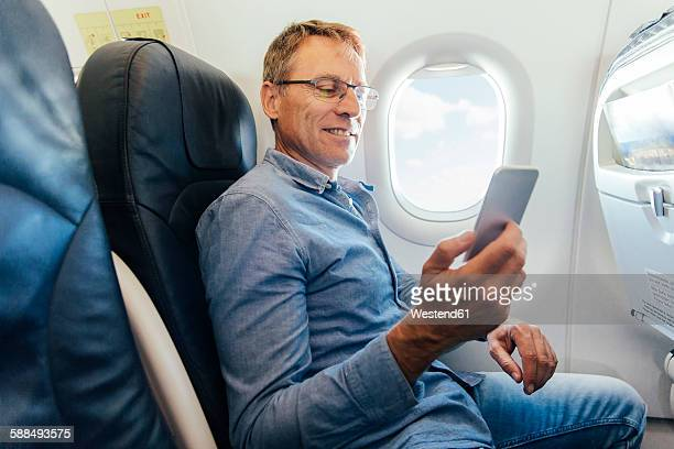 Mature man sitting on an airplane looking at his smartphone