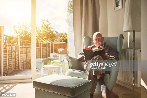 mature man sitting on arm chair and reading a book - reading stock pictures, royalty-free photos & images