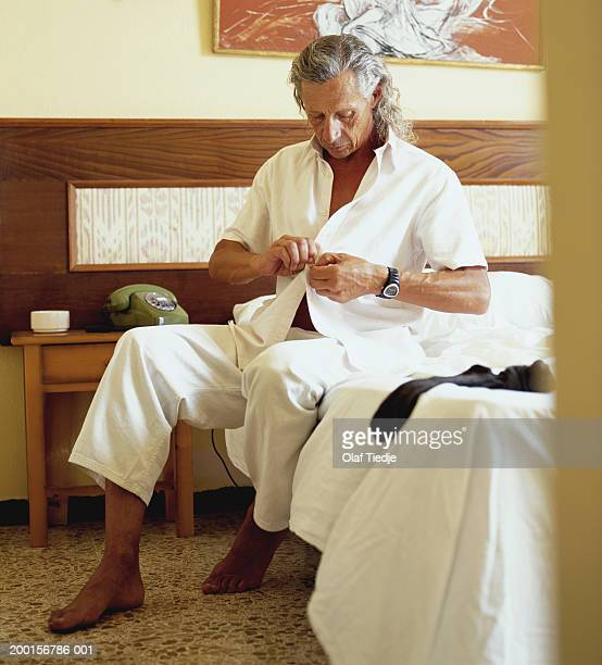 Mature man sitting on bed, buttoning shirt