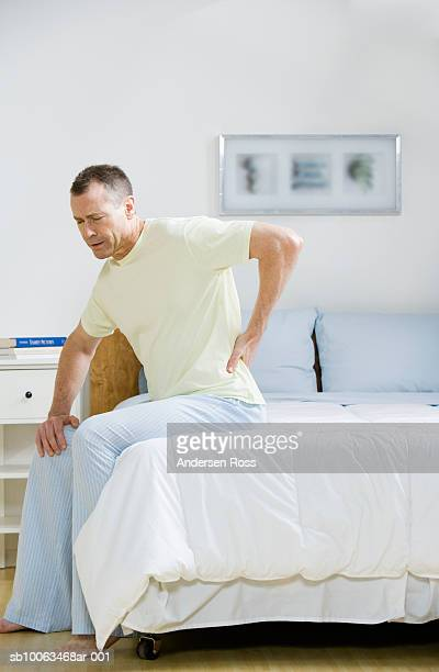 Mature man sitting on bed holding back