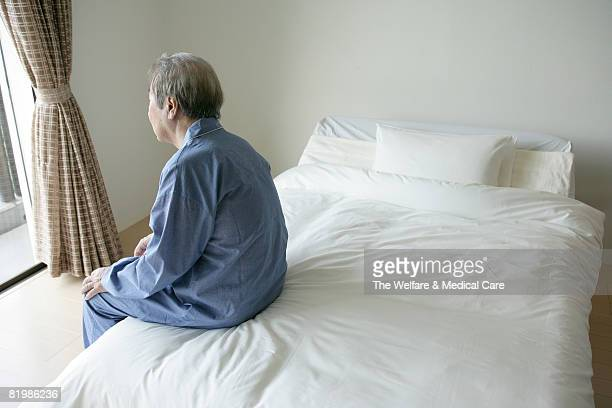Mature man sitting on bed