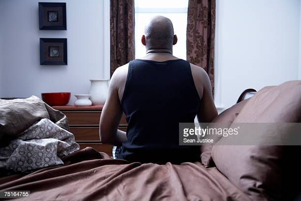 mature man sitting on bed, rear view - completely bald stock pictures, royalty-free photos & images