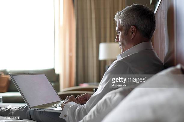 Mature man sitting on bed with laptop.