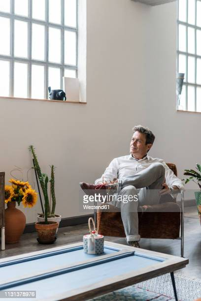 mature man sitting on chair in a loft thinking - one man only stock pictures, royalty-free photos & images
