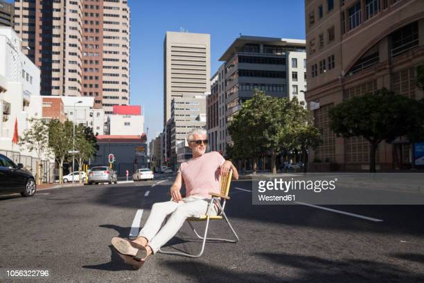 mature man sitting on chair in the street, wearing sunglasses - cadeira dobrável - fotografias e filmes do acervo