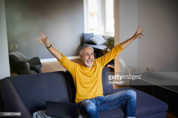 mature man sitting on couch at home cheering - arms raised stock pictures, royalty-free photos & images