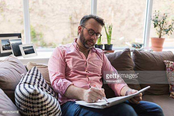 Mature man sitting on couch marking advertisments in newspaper